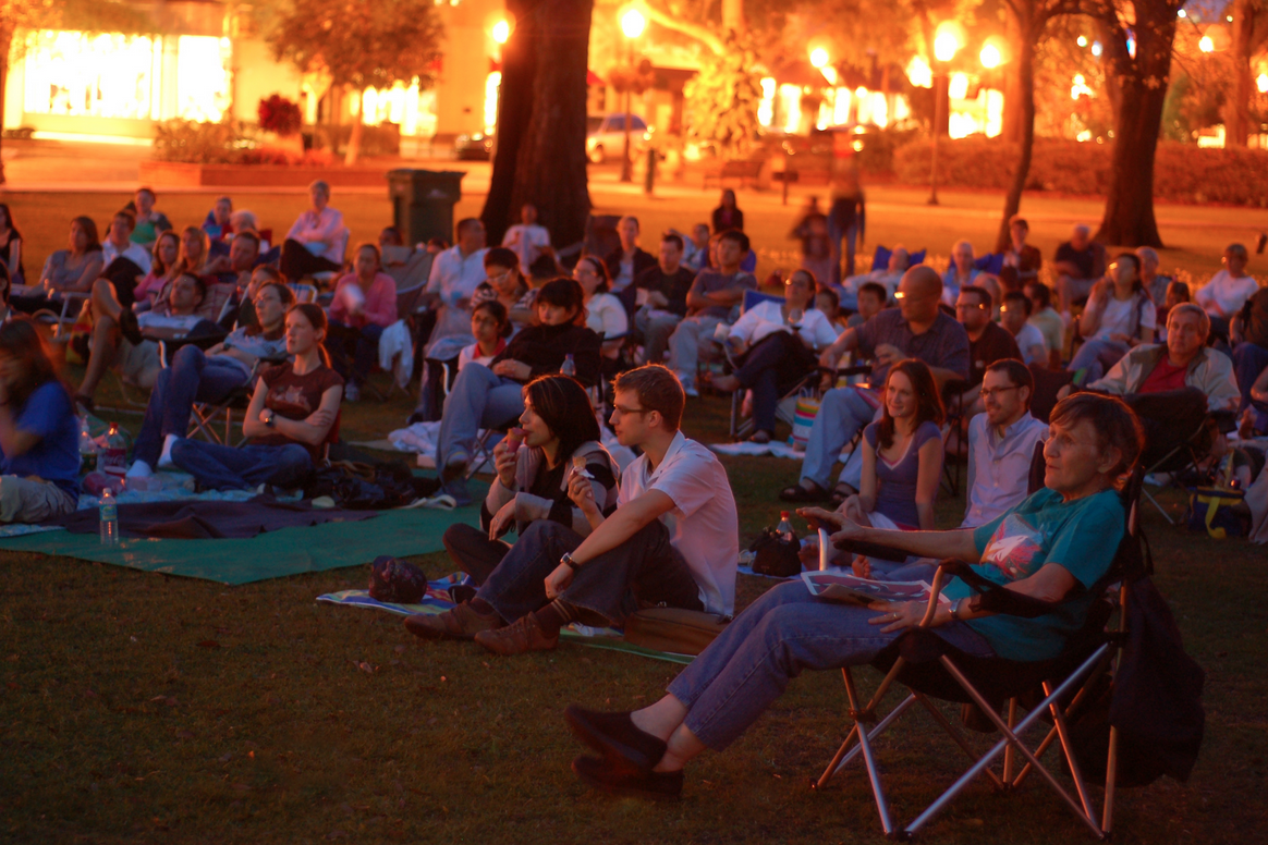 Things to in Orlando: image of people watching a free movie outdoors during Popcorn Flicks at the Park